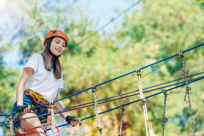 De vrouw draagt beschermende helm geniet van actieve vrije tijd in kabelpark stock foto's