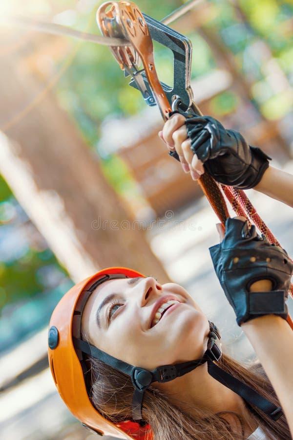 De vrouw draagt beschermende helm geniet van actieve vrije tijd in kabelpark stock afbeelding