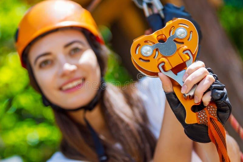 De vrouw draagt beschermende helm geniet van actieve vrije tijd in kabelpark royalty-vrije stock fotografie