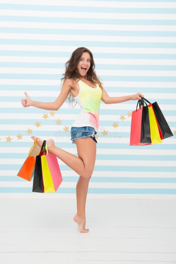 De vrouw draagt bos het winkelen zakken gestreepte achtergrond Tot slot gekocht favoriet merk De verkoop van de uiteindenwinkel T stock foto's