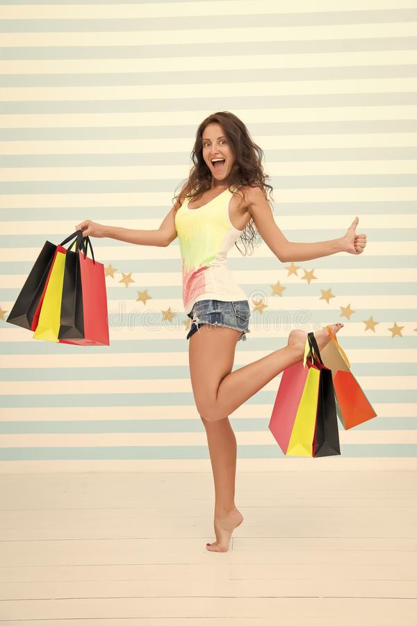 De vrouw draagt bos het winkelen zakken gestreepte achtergrond Tot slot gekocht favoriet merk De verkoop van de uiteindenwinkel T stock foto