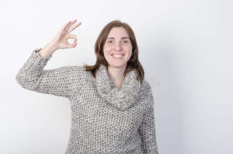 De vrouw draagt de winterkleren en maakt O.K. gebaar stock afbeelding