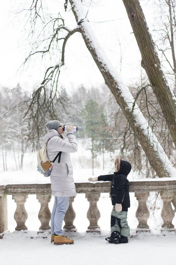 De vrouw drinkt buiten koffiecappuccino in de sneeuwwinter in koude wi royalty-vrije stock fotografie