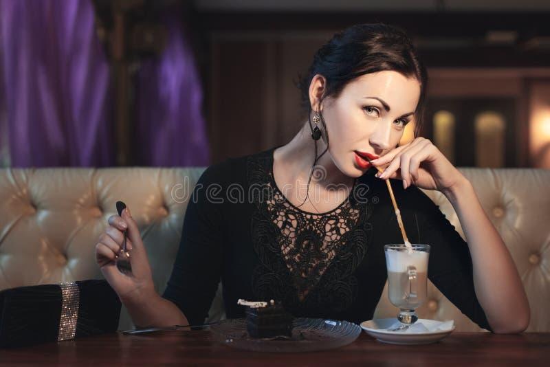 De vrouw drinkt koffie door een stro royalty-vrije stock afbeelding