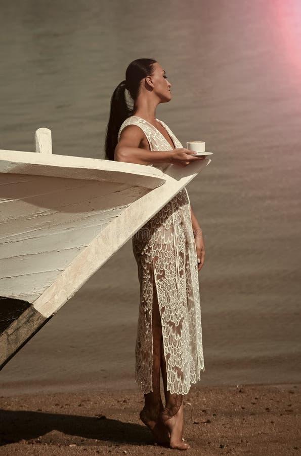 De vrouw drinkt koffie door de oceaan Vrouw bij jacht in witte kleding royalty-vrije stock afbeeldingen