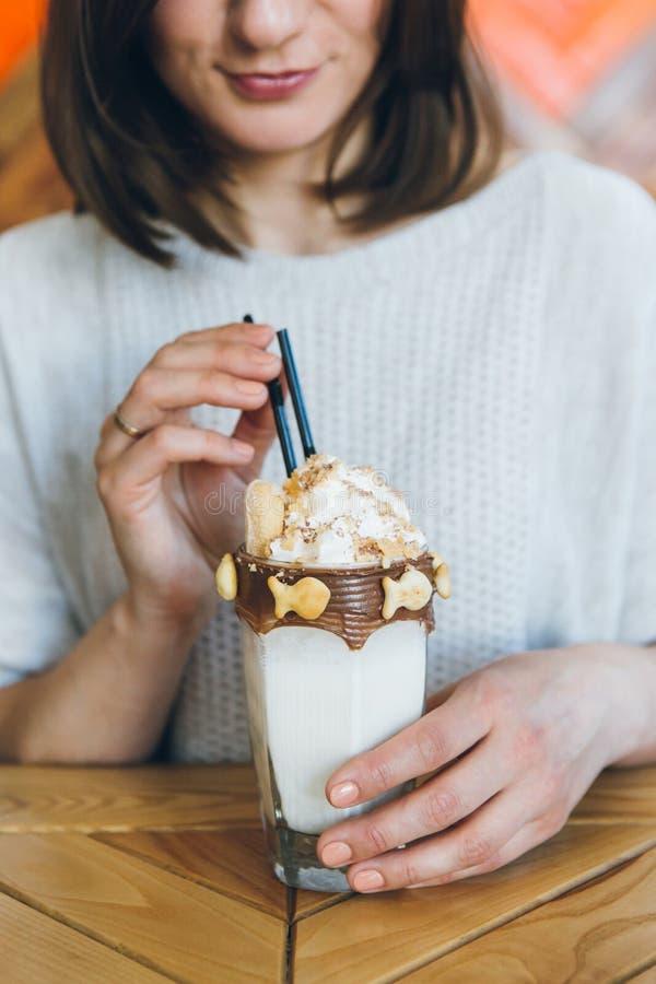 De vrouw drinkt milkshake die prachtig met room en koekjes wordt verfraaid royalty-vrije stock foto