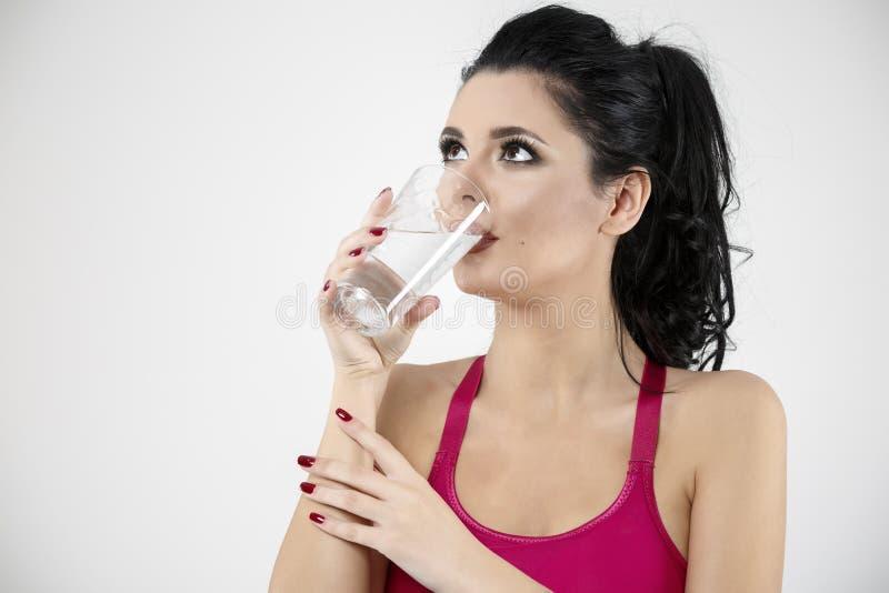 De vrouw drinkt water met glas stock foto's