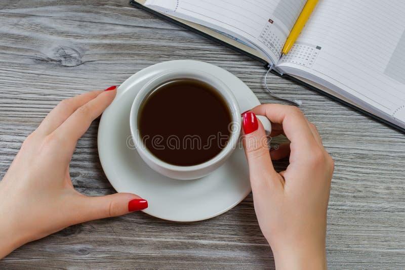 De vrouw drinkt weg thee terwijl het hebben van tijd van het schrijven en het bestuderen De commerciële van de pauzeonderbreking  royalty-vrije stock foto's