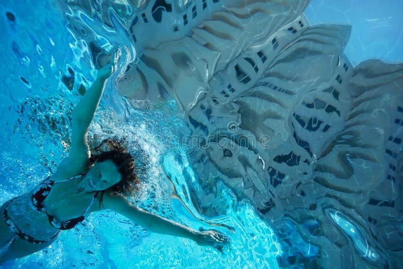 De vrouw duikt onderwater met gesloten ogen stock foto's