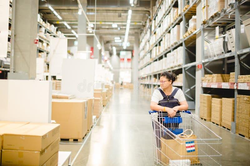 De vrouw duwt een boodschappenwagentje in pakhuis voor het winkelen royalty-vrije stock afbeelding