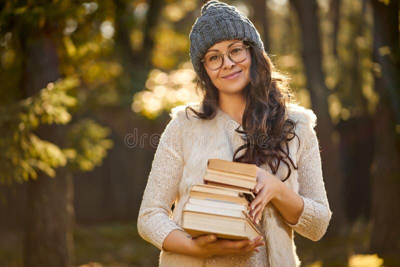 De vrouw in een GLB en glazen houdt een stapel van boeken op de achtergrond van de herfstbos stock foto