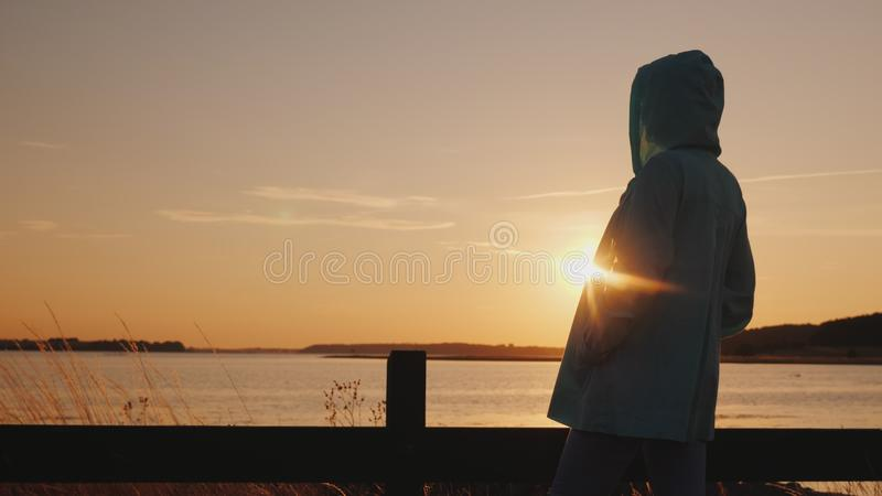 De vrouw in een de herfstjasje met een kap bewondert de zonsondergang over het meer stock foto