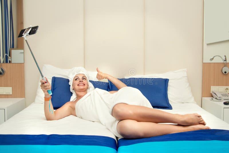 De vrouw in een hotelruimte neemt een selfiefoto op hun mobiele telefoon royalty-vrije stock afbeeldingen