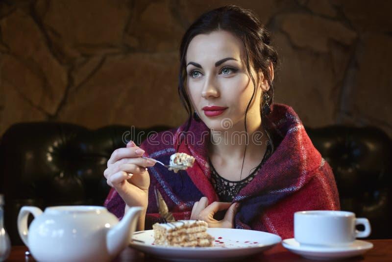 De vrouw in een koffie eet cakes royalty-vrije stock foto