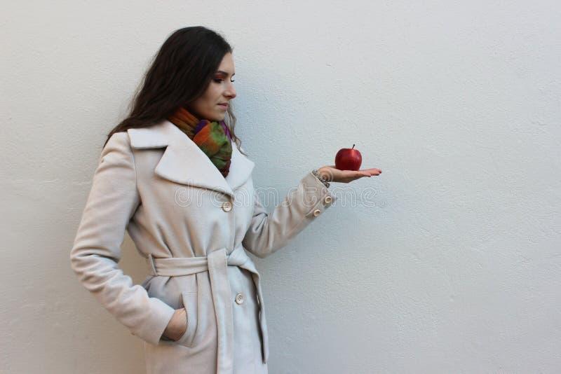 De vrouw in een laag houdt en kijkt een rode sappige appel royalty-vrije stock foto's