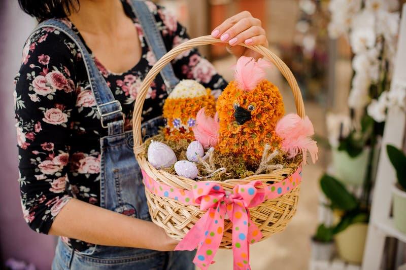 De vrouw een Pasen-gift houden die bestaand uit rieten mand met kip en eivorm bloeit royalty-vrije stock fotografie