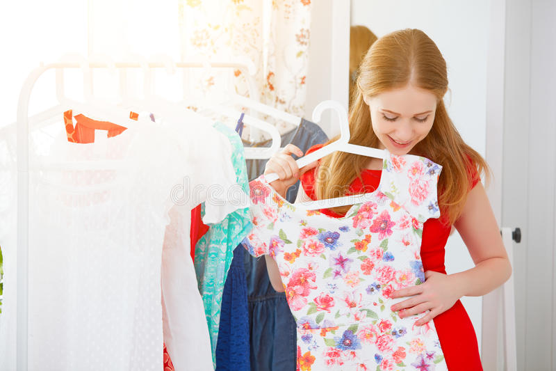 De vrouw in een rode kleding kijkt in de spiegel en kiest kleren royalty-vrije stock afbeeldingen