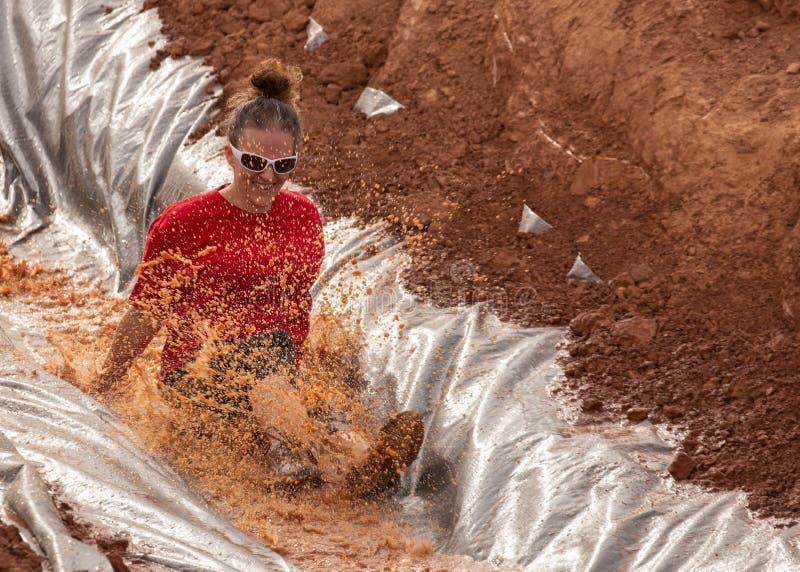 De vrouw in een rood overhemd en de zonnebril die onderaan een water glijden glijden binnen een de hinderniscursus van de modderl royalty-vrije stock fotografie