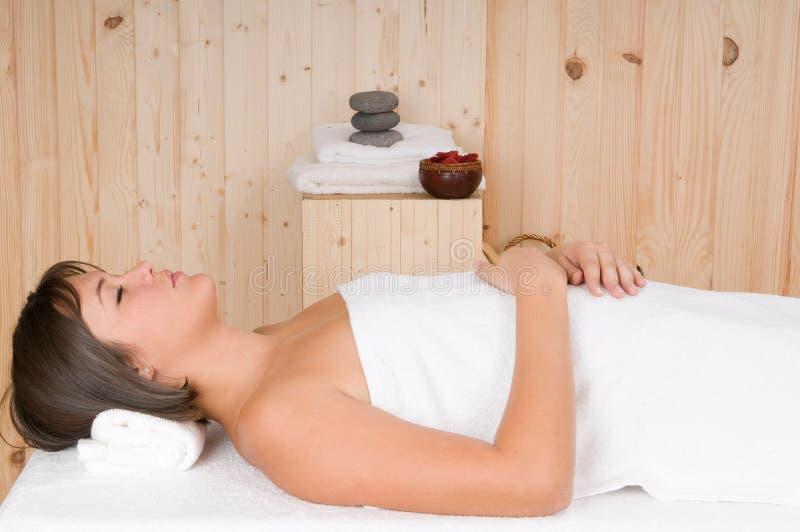 De vrouw in een sauna of ontspant massagezitting stock fotografie