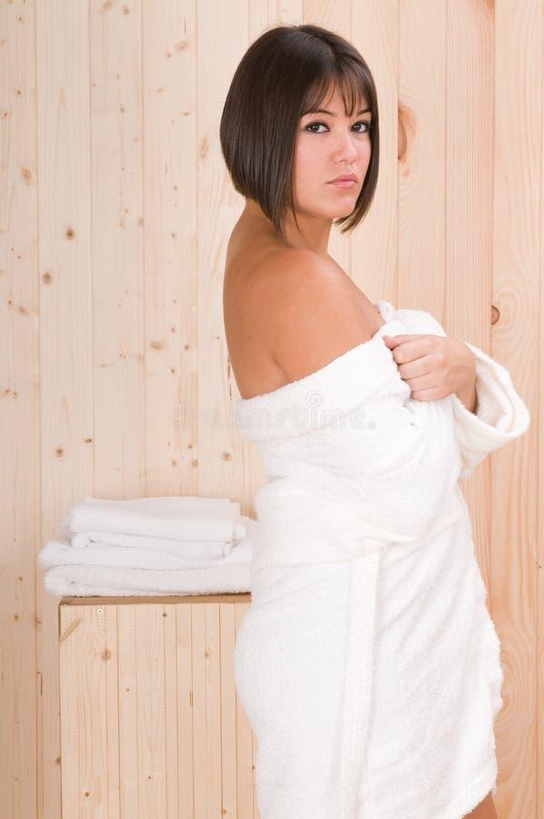 De vrouw in een sauna of ontspant massagezitting stock foto