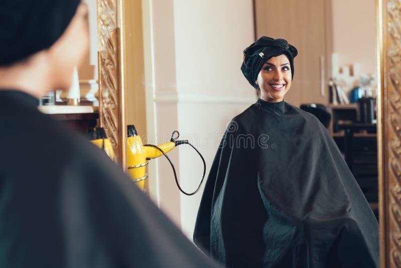 De vrouw in een schoonheidssalon bekijkt haar gedachtengang in de spiegel stock foto's