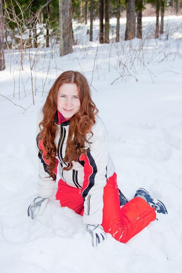 De vrouw in een sportief kostuum zit op sneeuw in-gebied royalty-vrije stock afbeelding