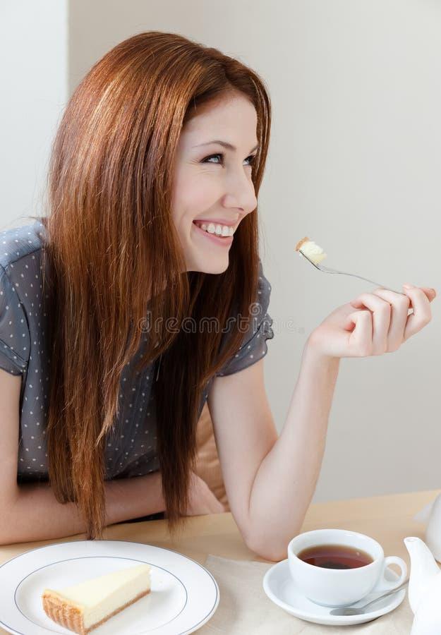 De vrouw eet de cake bij de koffie stock foto