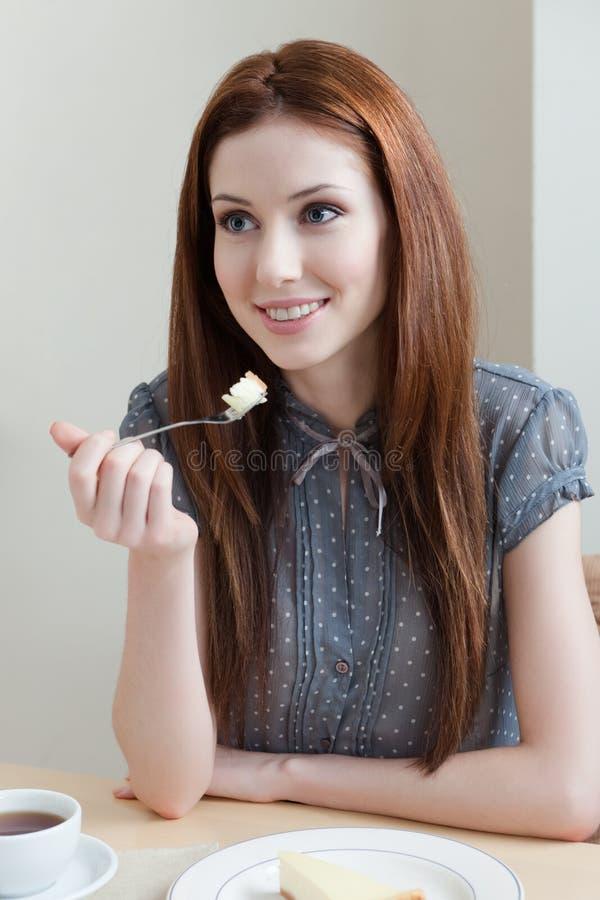 De vrouw eet de pastei bij de koffie royalty-vrije stock afbeelding