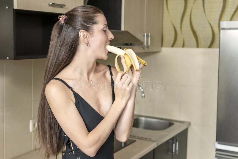 De vrouw eet seksueel een banaan stock foto