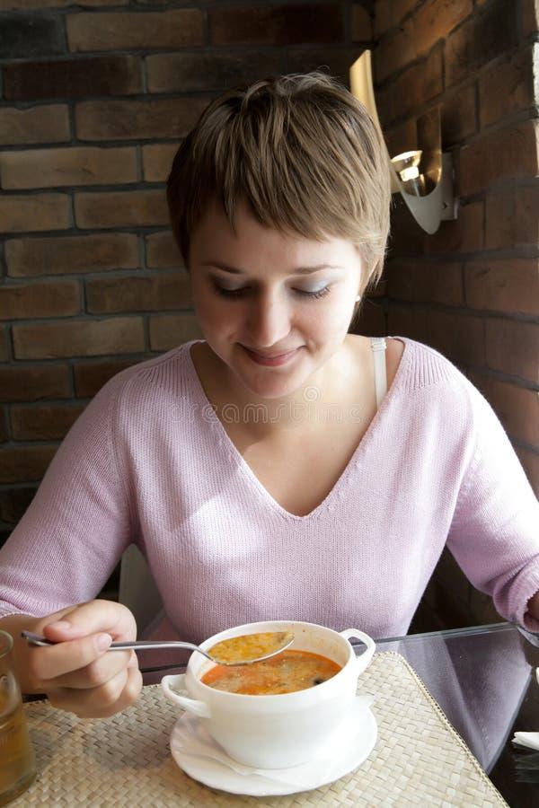 De vrouw eet soep stock foto's