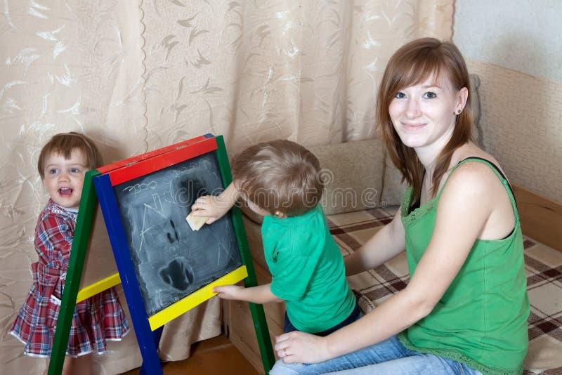 De vrouw en de kinderen trekken op bord stock afbeeldingen