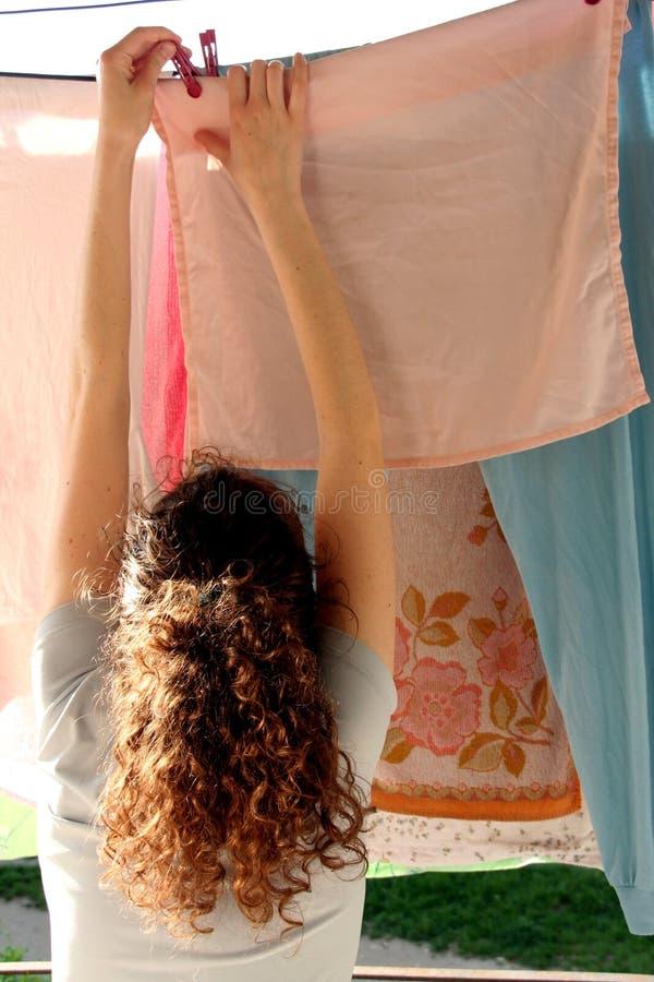De vrouw en de wasserij van het huis stock fotografie