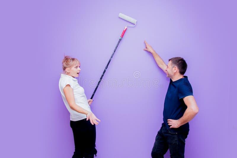 De vrouw en de echtgenoot schilderen de muur met een rol royalty-vrije stock fotografie
