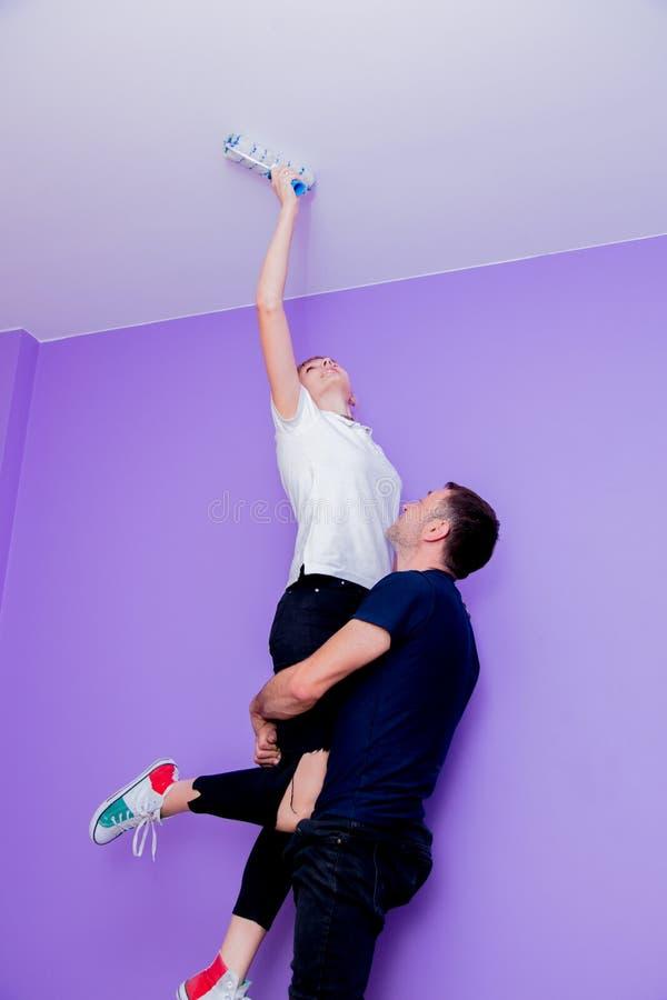 De vrouw en de echtgenoot schilderen de muur met een rol stock afbeeldingen
