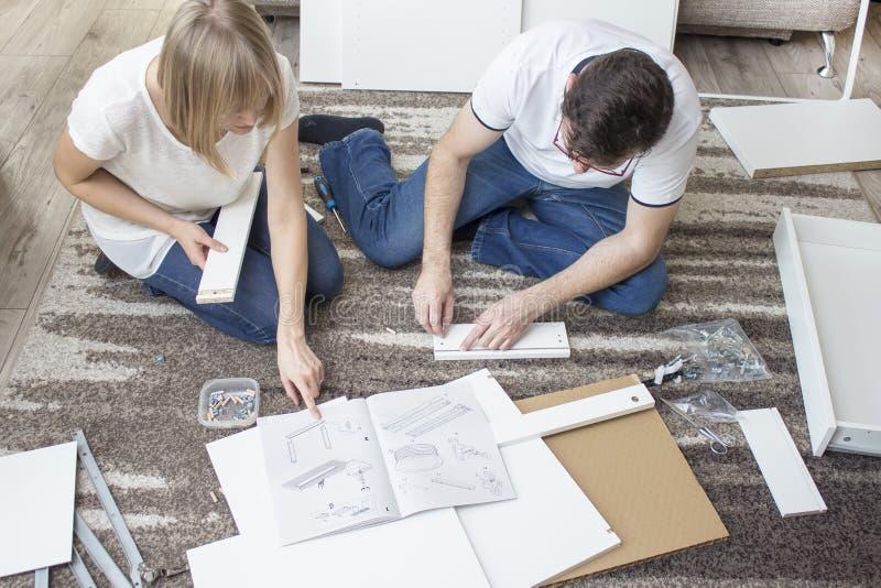 De vrouw en een man in jeans en witte T-shirts zitten op het tapijt in de woonkamer van het vlakte en draai witte meubilair royalty-vrije stock fotografie
