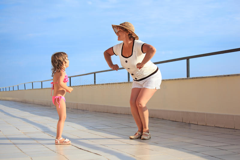 De vrouw en girl do morning oefenen op veranda uit stock foto's