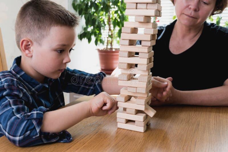 De vrouw en het jonge geitje spelen jengaspel Het proberen om saldo van toren van houten blokken te houden De tijd van familielea royalty-vrije stock foto