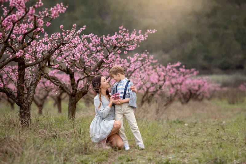De vrouw en de jongen bevinden zich door struik van sering te bloeien Zij ruikt bloemen familie tijd samen royalty-vrije stock foto's