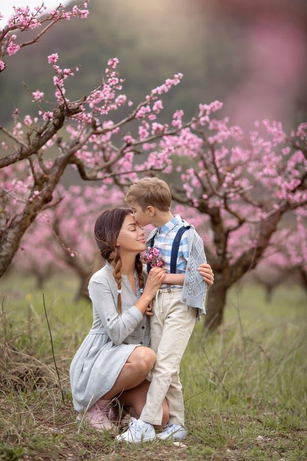 De vrouw en de jongen bevinden zich door struik van sering te bloeien Zij ruikt bloemen familie tijd samen stock foto