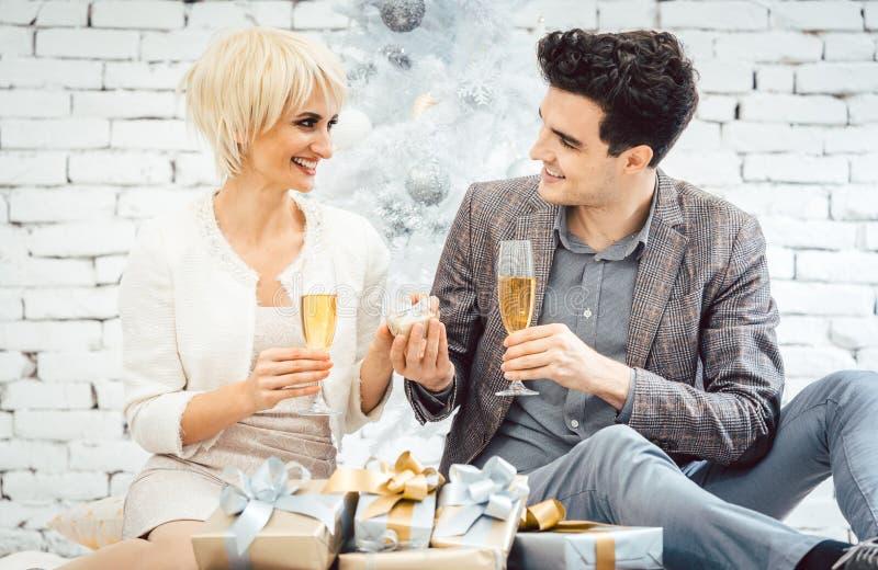 De vrouw en de man met wijn en stellen voor witte Kerstboom voor stock foto's