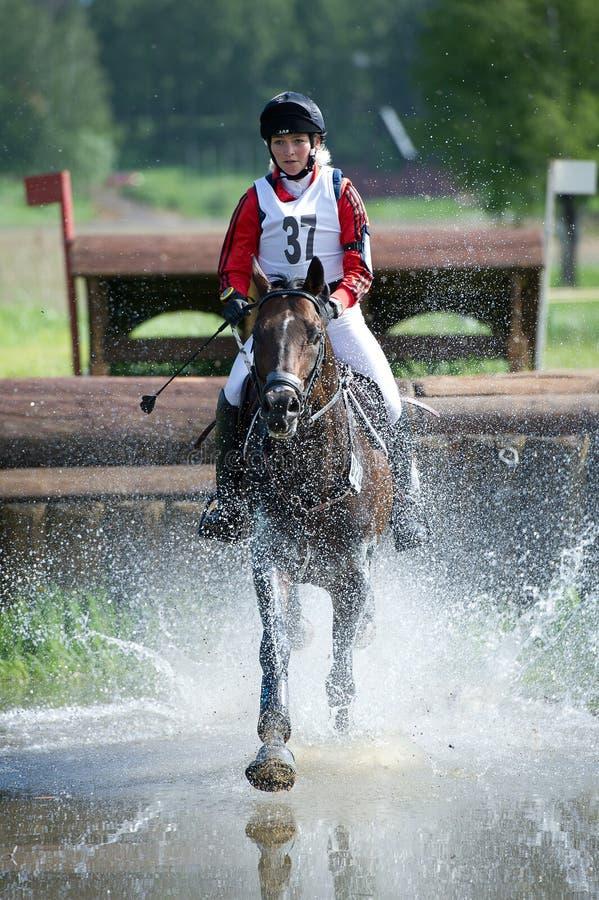 De vrouw eventer op paard wordt in werking gesteld in Watersprong stock fotografie