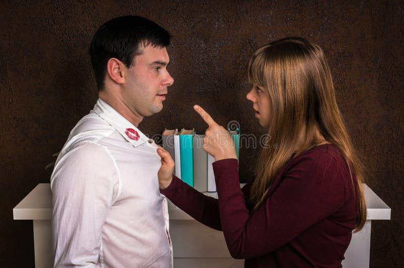 De vrouw finded rode lippenstift op overhemdskraag - ontrouwconcept royalty-vrije stock afbeelding