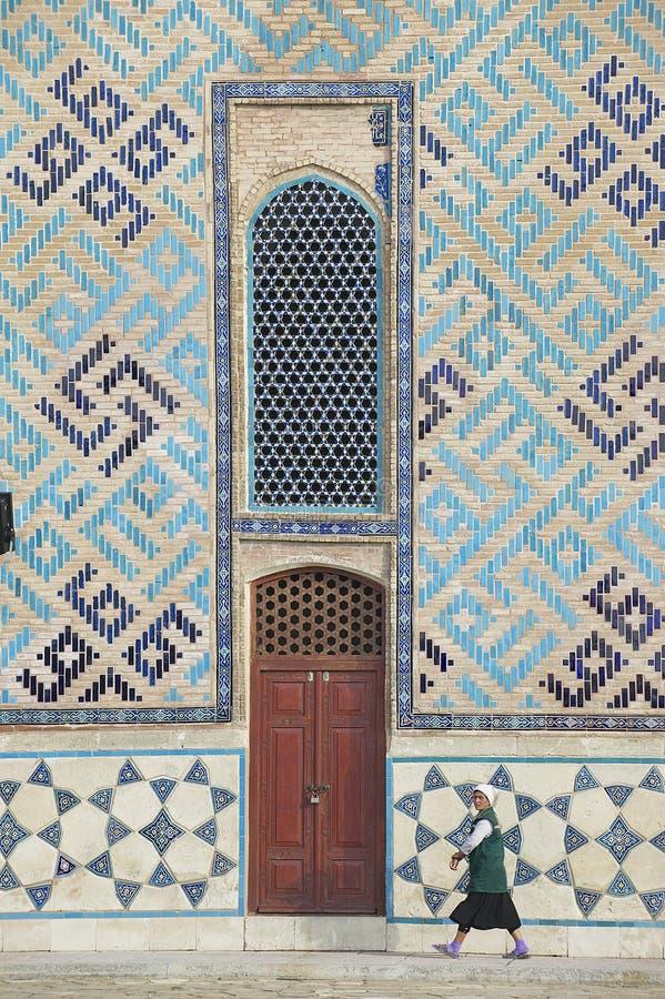 De vrouw gaat door de muur van het mausoleum van Khoja Ahmed Yassawi in Turkistan over, Kazachstan stock afbeelding