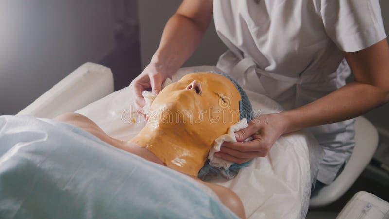 De vrouw gaat het masker van het behandelingsfruit gezichts bij de schoonheidssalon over stock fotografie