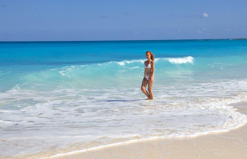 De vrouw gaat op kust van oceaan royalty-vrije stock afbeelding