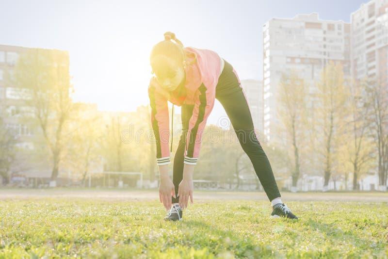 De vrouw gaat sporten die aan de voet leunen royalty-vrije stock fotografie