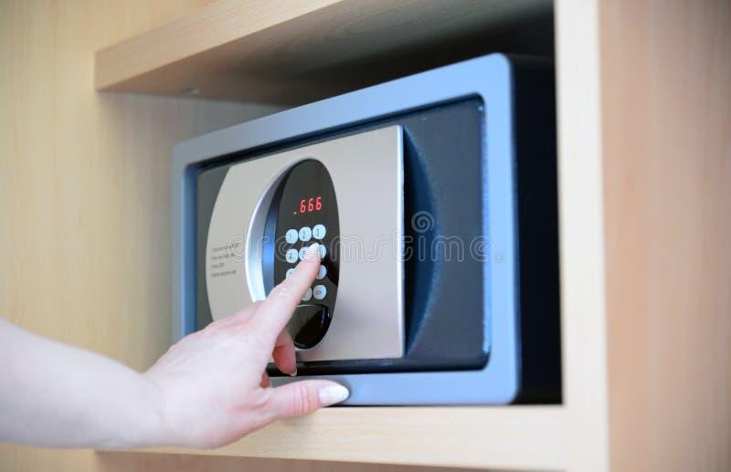 de vrouw gebruikt een brandkast in hotel stock afbeelding
