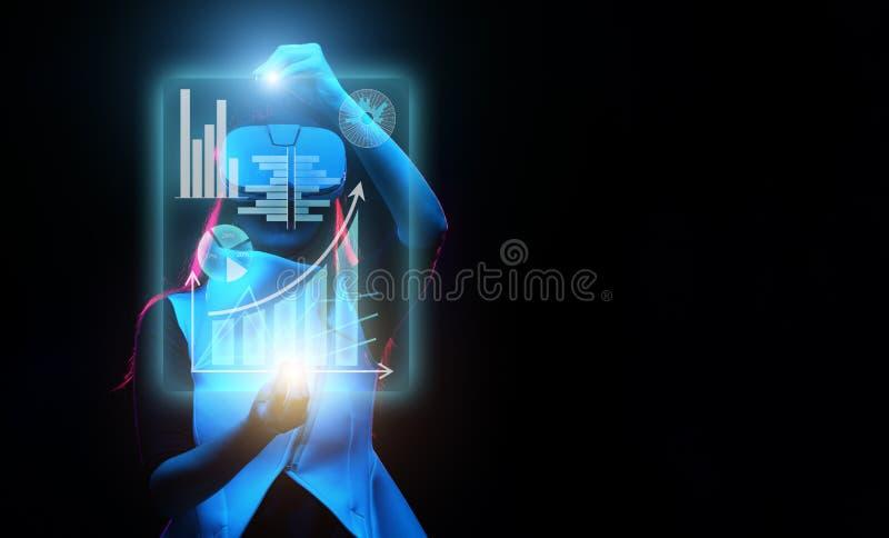 De vrouw gebruikt een virtuele werkelijkheidshoofdtelefoon om met gegevens in de vorm van grafieken en grafieken te werken stock afbeelding