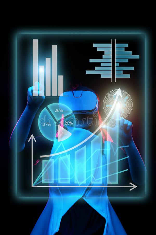 De vrouw gebruikt een virtuele werkelijkheidshoofdtelefoon om met gegevens in de vorm van grafieken en grafieken te werken stock afbeeldingen