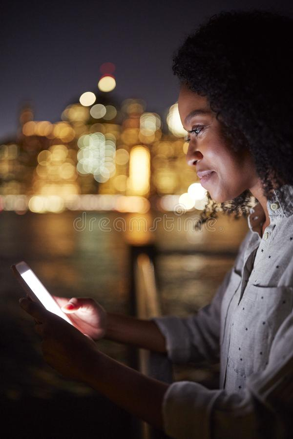 De vrouw gebruikt Mobiele Telefoon bij Nacht met Stadshorizon op Achtergrond stock foto's
